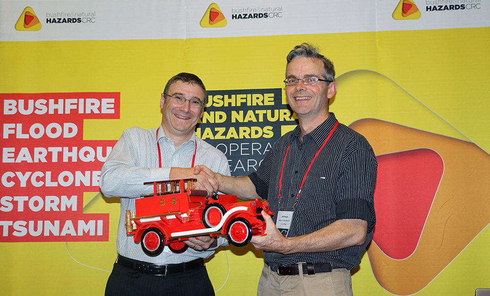 Dr Jeff Kepert (right) with his new fire truck prize, with CEO Dr Richard Thornton.