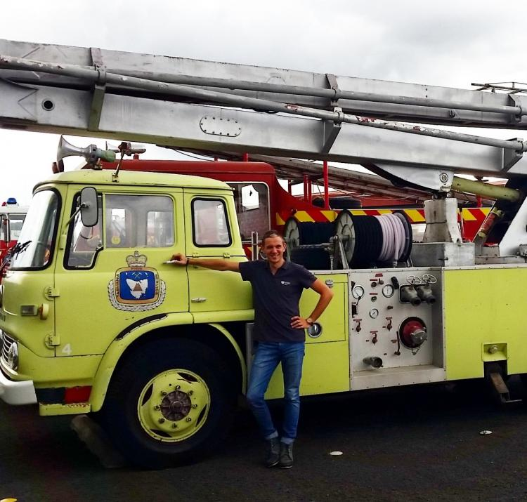 PhD student Billy Haworth with a retro fire tanker in Launceston, while on placement at Tasmania Fire Service