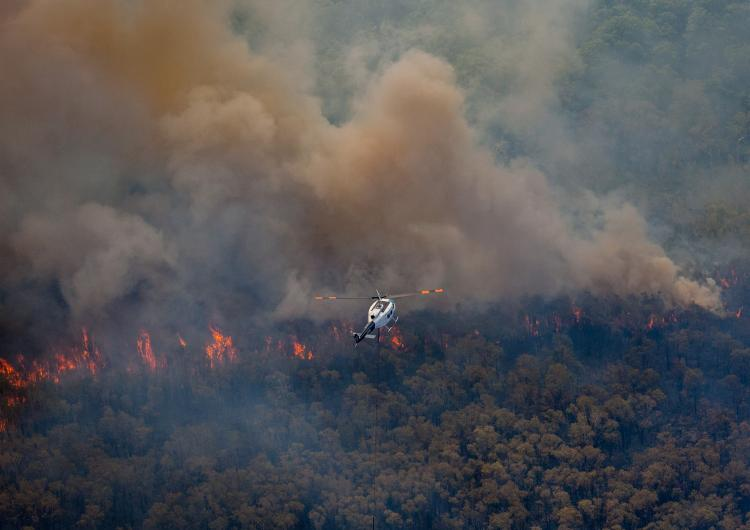 Firefighting helicopter flying over the 2018 Stradbroke bushfires. Photo: QFES