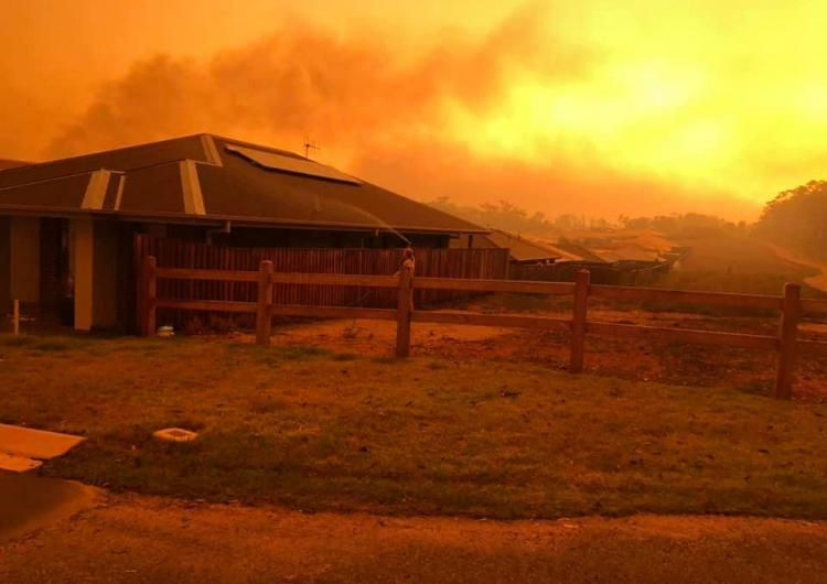 A women hoses her roof while the Lindfield Park Road bushfire threatens. Photo: NSW Rural Fire Service
