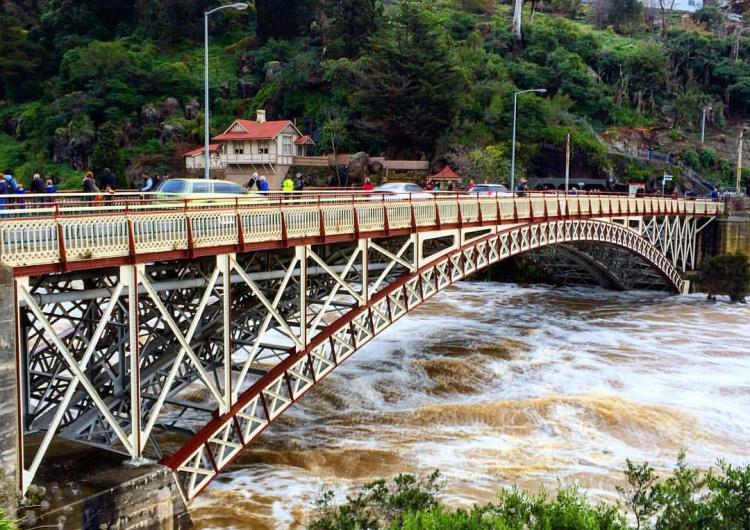 Floodwaters rage below Kings Bridge, Launceston. Photo Flickr upsticksngo_crew