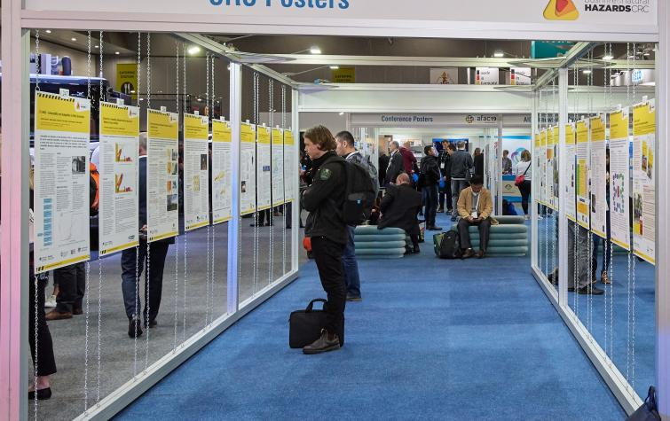 A conference participant views CRC posters in the exhibition hall at AFAC19 in Melbourne.