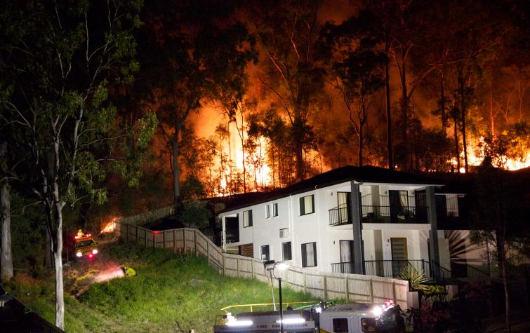A bushfire rages behind a Brisbane home. Photo: HighExposure (CC BY-NC-ND-2.0)