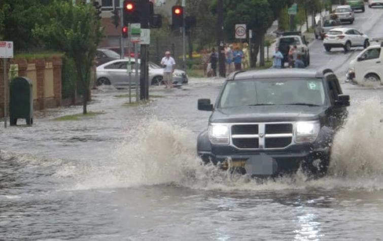 A car trying to make its way through flooding in Hawthorn Rd, Brighton East. Photo: Peter Farrar.