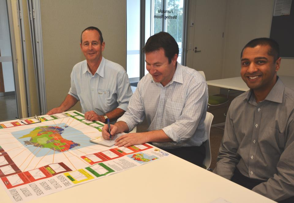 Fire managers consulting at a fire seasonality map at a seasonal bushfire outlook workshop. Photo: Bushfire and Natural Hazards CRC