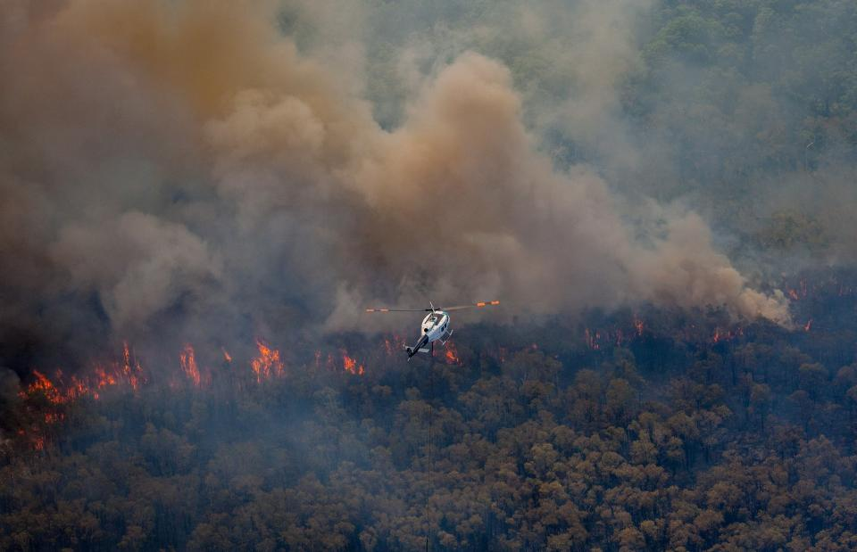 Firefighting helicopter flying over the 2018 Stradbroke bushfires.