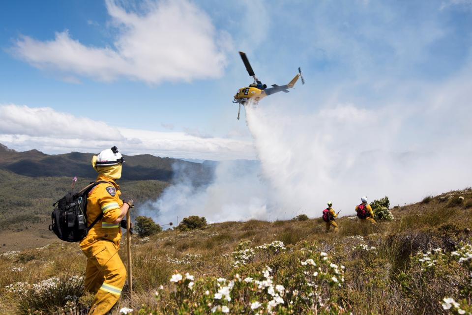 Tasmanian remote area firefighters and water bombing aircraft working on the Gell River bushfire at Mount Wright, 11 January 2019 Photo: Warren Frey TFS.